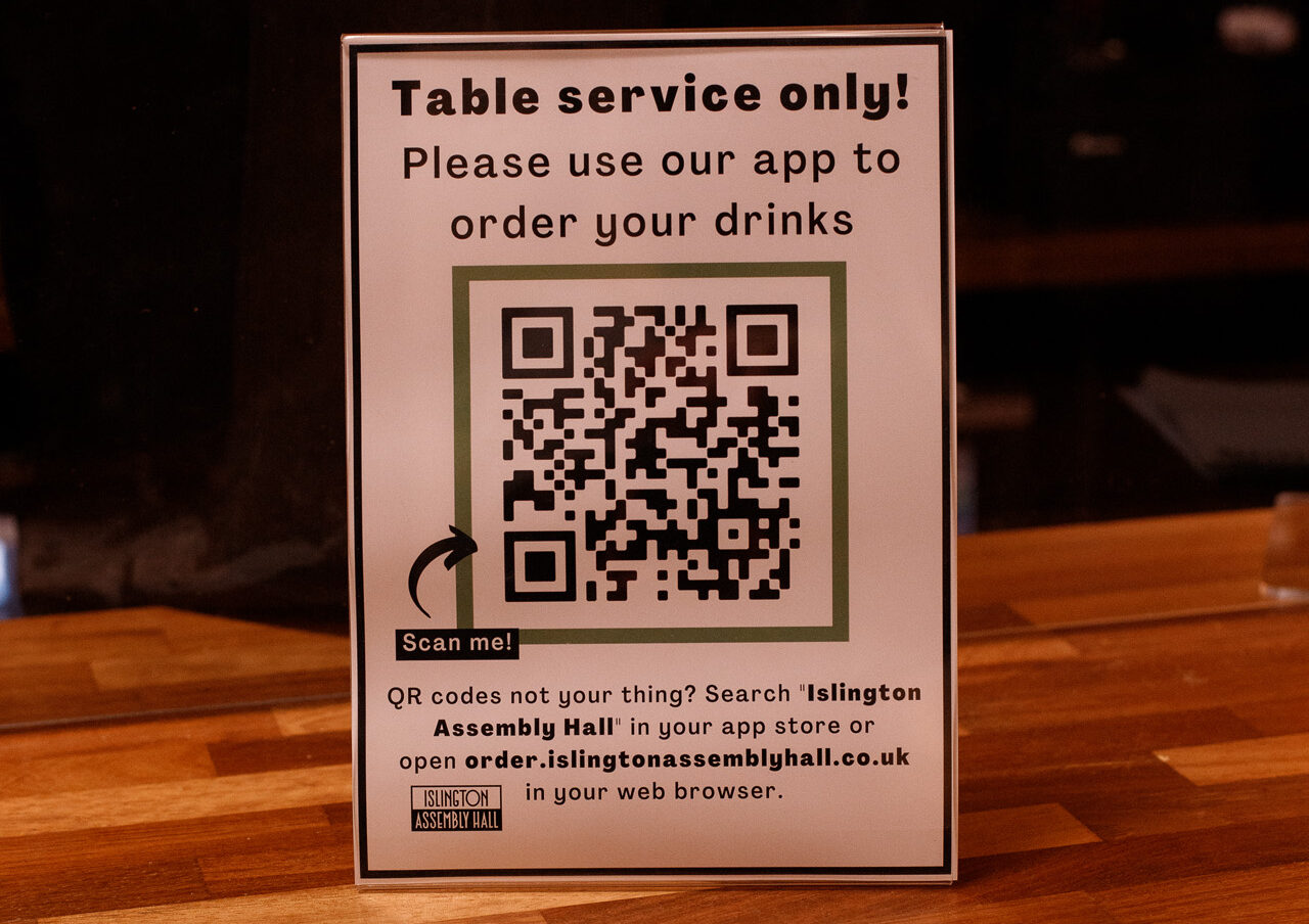 Poster standing on a bar top directing customers to download our app in order to buy drinks for table service